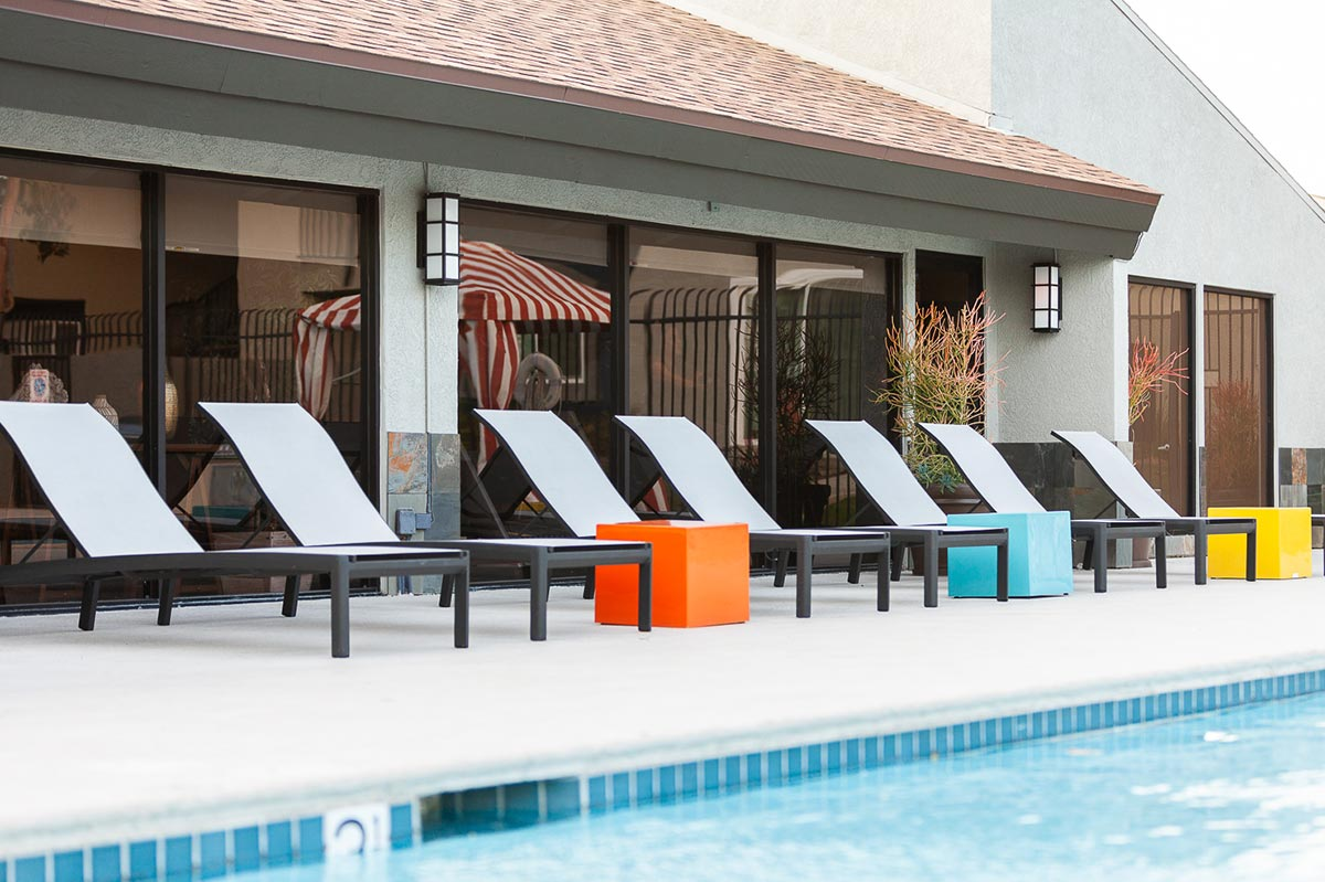 Poolside lounge chairs next to apartment complex