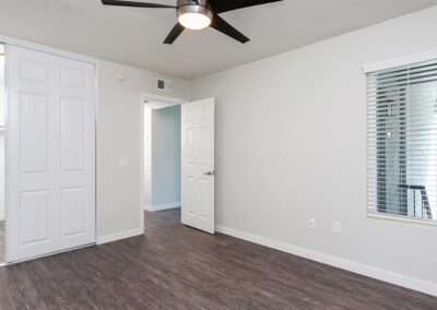 Empty Bedroom area with ceiling fan and windows