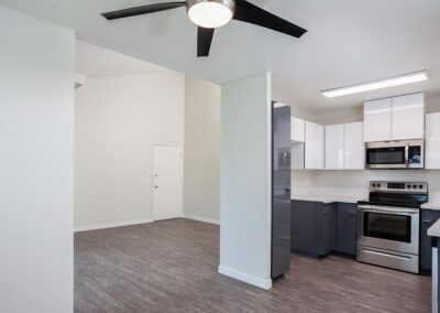 Kitchen and dining room with ceiling fan and wood floors